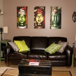 Living room scene with three Buddhas highlighted above the sofa